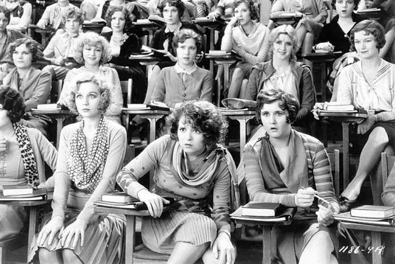 Still from the film The Wild Party with a group of women sitting in a lecture theatre looking toward the front with various extreme expressions
