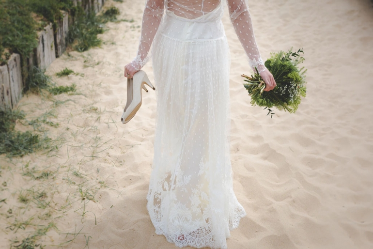 Woman in wedding dress walking on beach from married at first sight reality show
