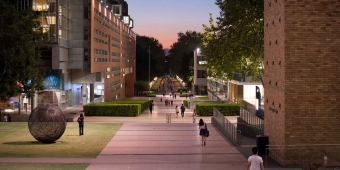 Students walk down the UNSW outdoor mall at dusk.