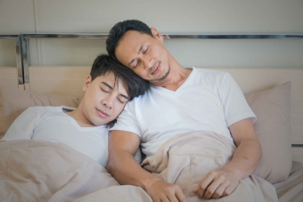 Two Asian men resting in bed.