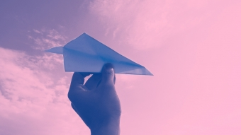 Hand throwing a paper airplane in a pink sky.