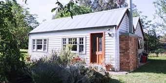 Small blue weatherboard house with a small garden. Photo: Unsplash