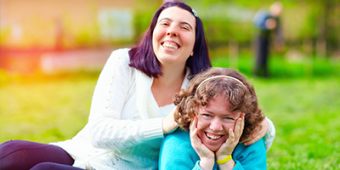 Two women sitting on the grass, smiling at the camera. Photo: BigStock