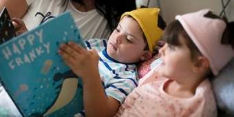 Two children reading a book in bed. Photo: BigStock