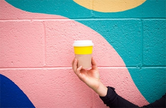 Yellow coffee cup being held against artistic wall