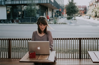 Student working at a laptop at an outdoor cafe