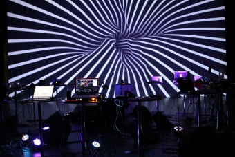 A lineup of computers in front of a screen with a spiral image projected on it.