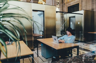 Man with black beanie sitting in empty office on laptop