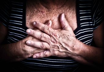 An older woman covers her chest with her hands.