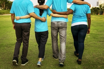 Four adults in blue t-shirts volunteering and embracing