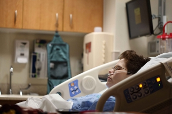 Woman lying in hospital bed.