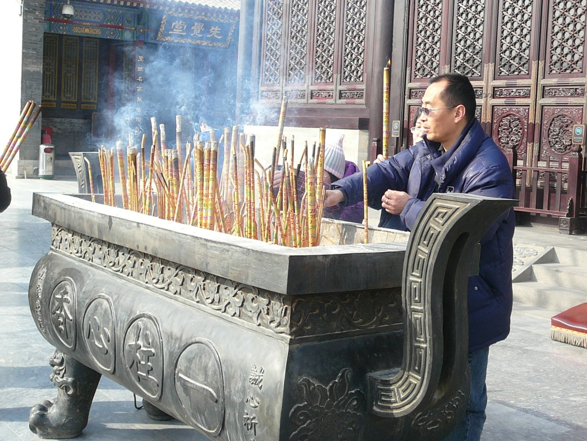 A Chinese worshipper lighting joss sticks at the Giant Wild Goose Pagoda in Xi'an, China​