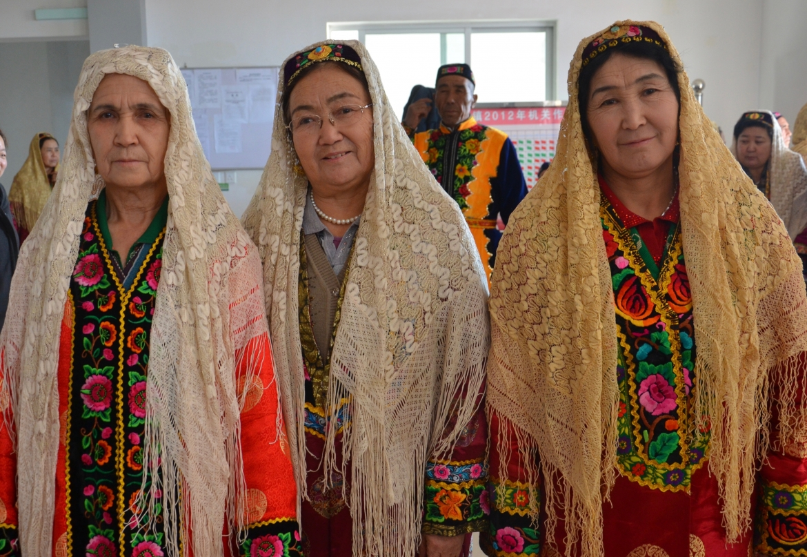 Uyghur women in traditional clothes getting ready for Nawruz celebration. Qomul, Xinjiang Uyghur Autonomous Region, China.​