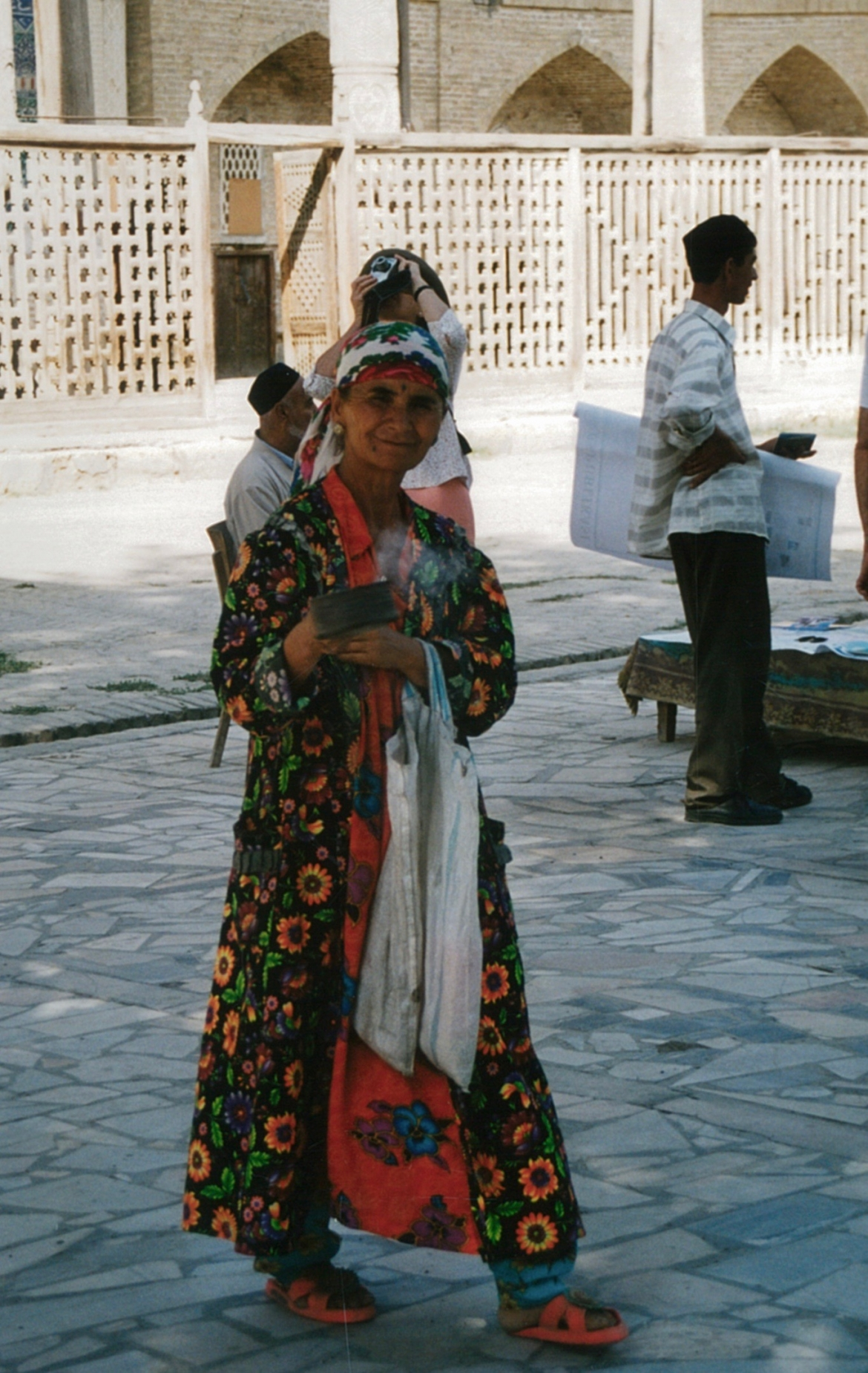 Gypsy woman blessing the passersby with sacred smoke, Samarkand, Uzbekistan.​