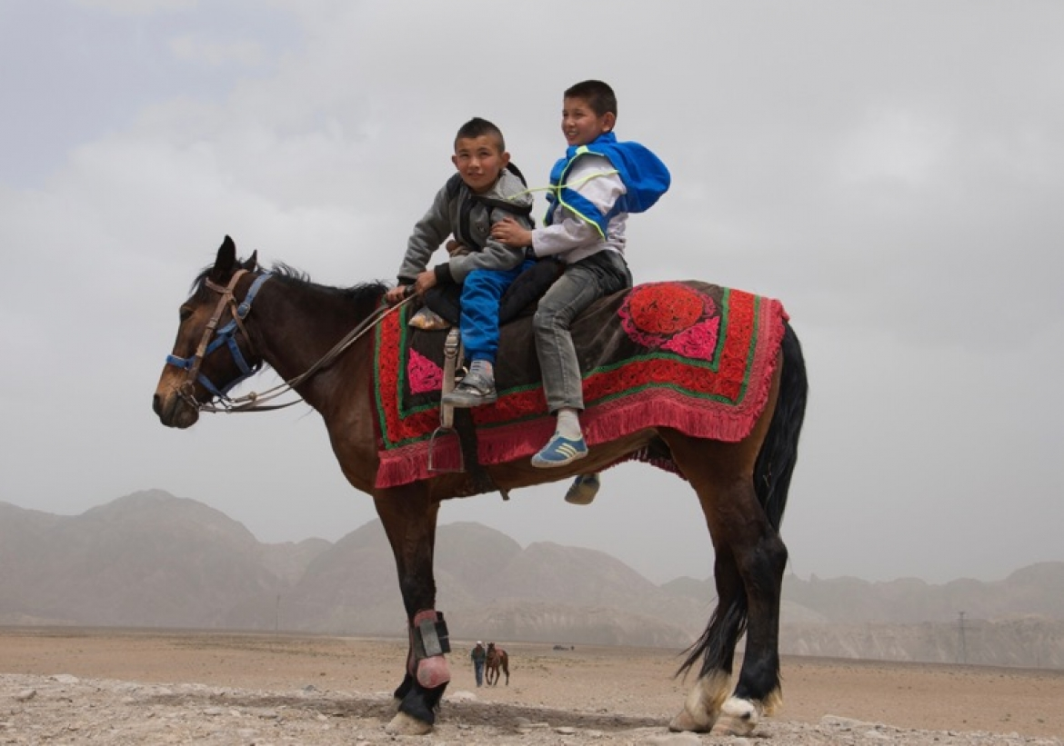 Young Kyrgyz riders getting ready for the horse games. Atush, Xinjiang Uyghur Autonomous Region, China.​  ​