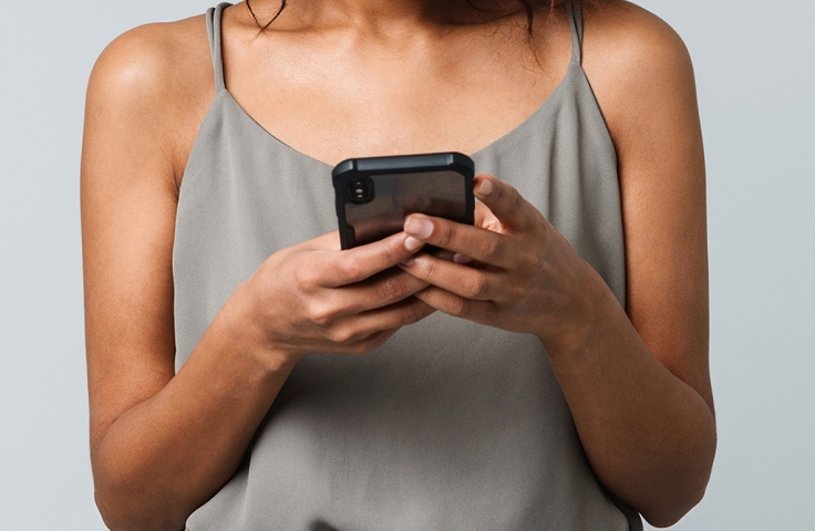 close up torso of woman holding mobile phone