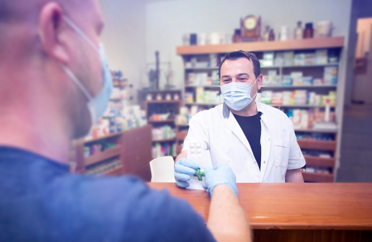 Person in protective medical mask buys medicine from a pharmacist
