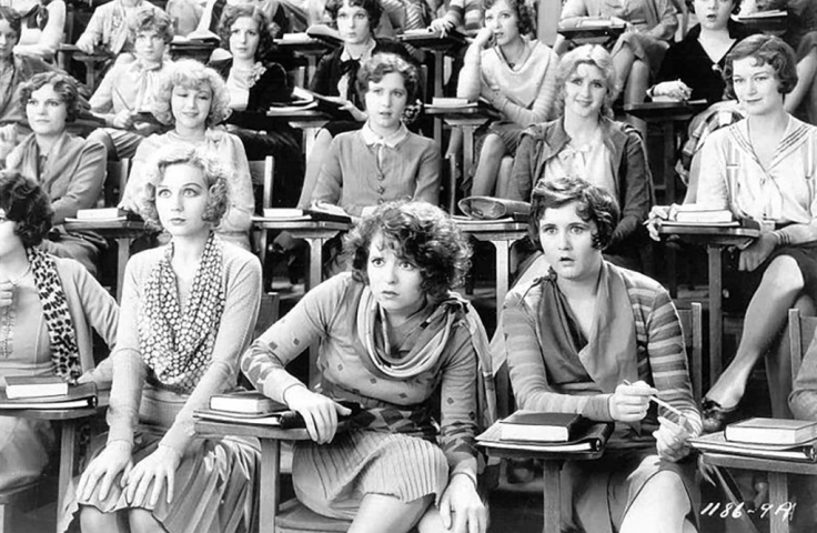 still from the film The Wild Party with a group of women sitting in a lecture theatre looking towards the front with various extreme expressions
