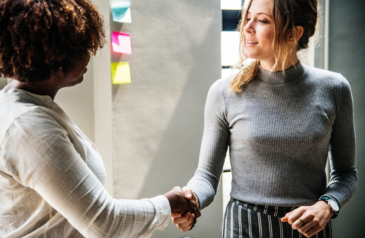 Two women shaking hands and forming an industry partnership