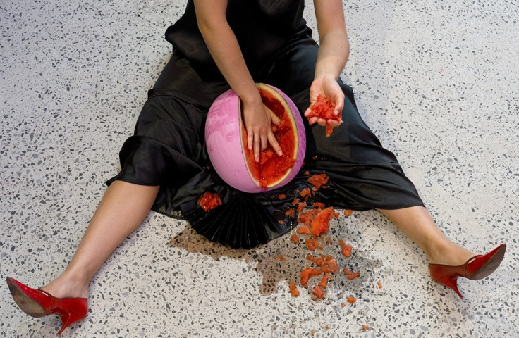 A woman scoops out a watermelon.