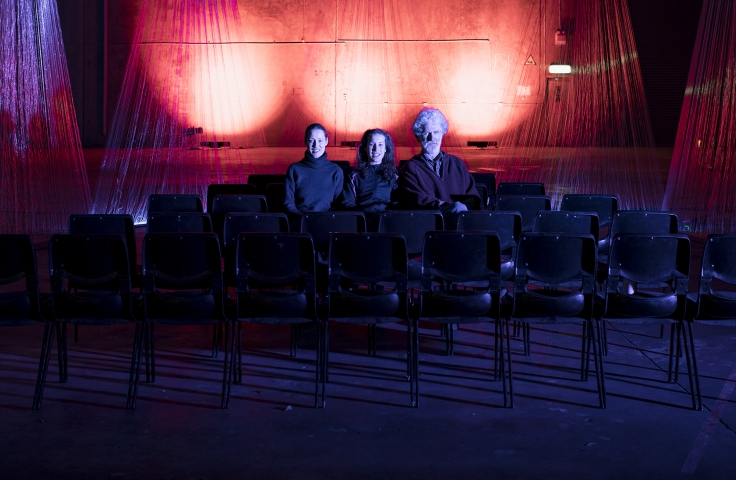 Three people sitting in a theatre