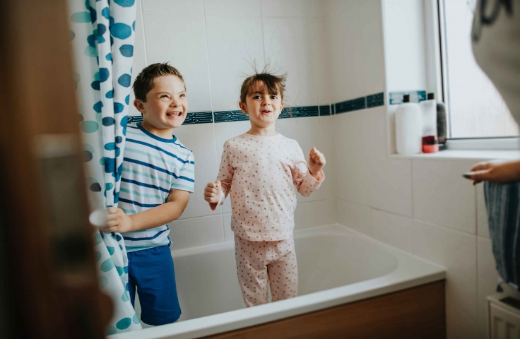 Young boy and girl playing hide and seek in the bathroom.