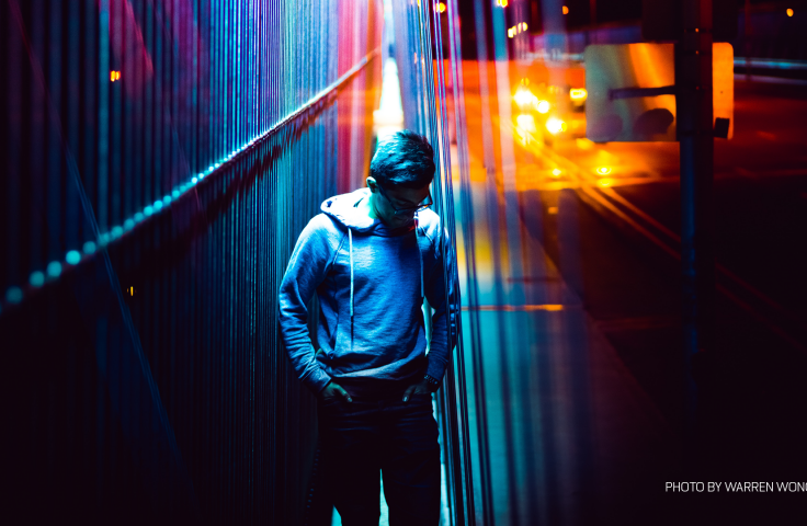 Teenager standing on a bridge under rainbow neon lights.