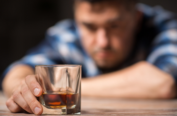 Shot of rum in glass with blurred man in background
