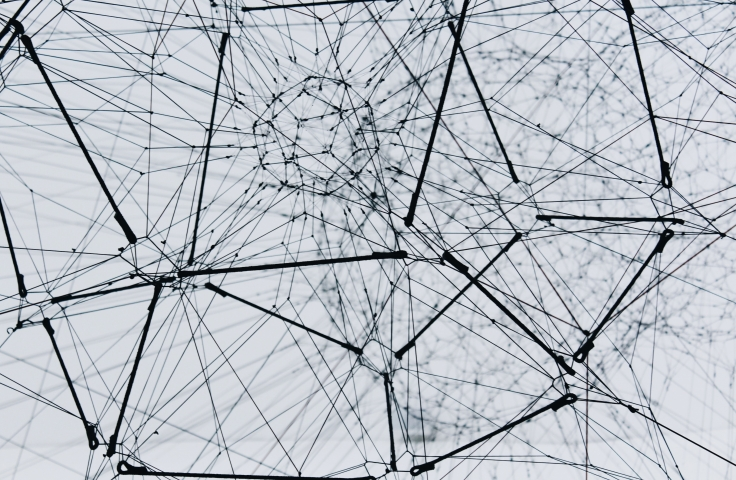 Photo of an abstract network outlined in black string on a white background.