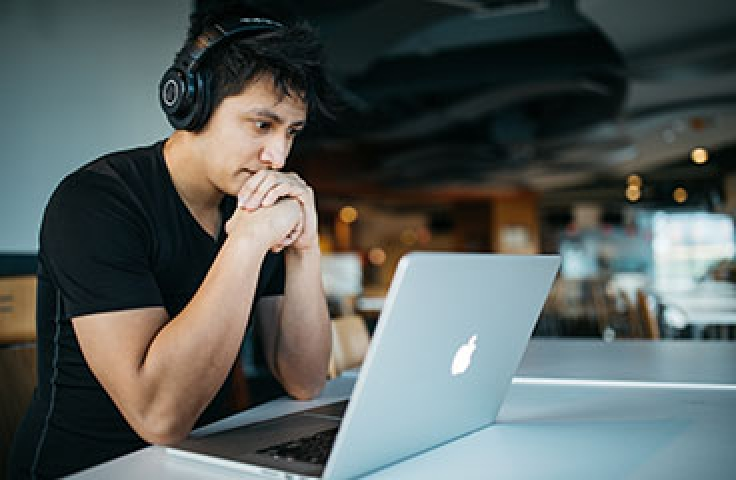 Bachelor of Commerce student sitting at laptop with headphones reviewing course material