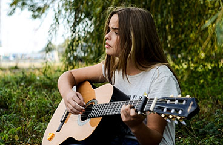 Woman outside playing music on the guitar