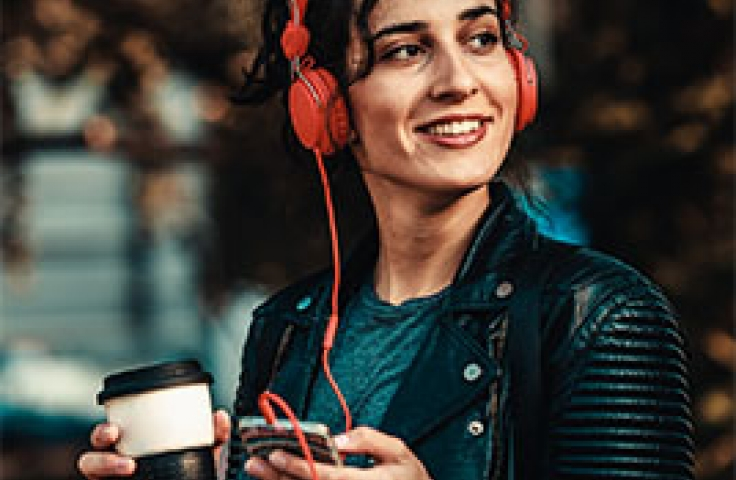 Woman with cup of coffee wearing red earphones in the city