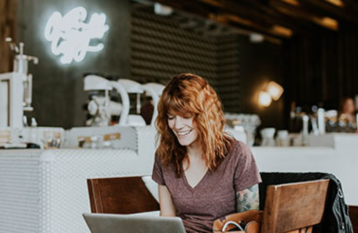 Smiling woman with red wavy hair sitting in coffee shop