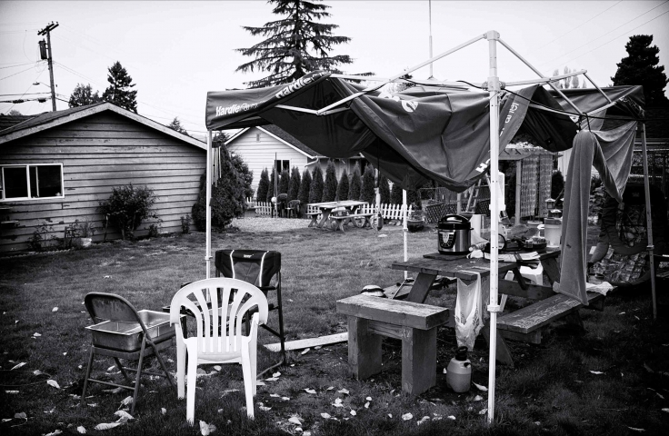 A white plastic garden chair sits under a broken marquee in a backyard. Photo: Joni Gutierrez, Unsplash