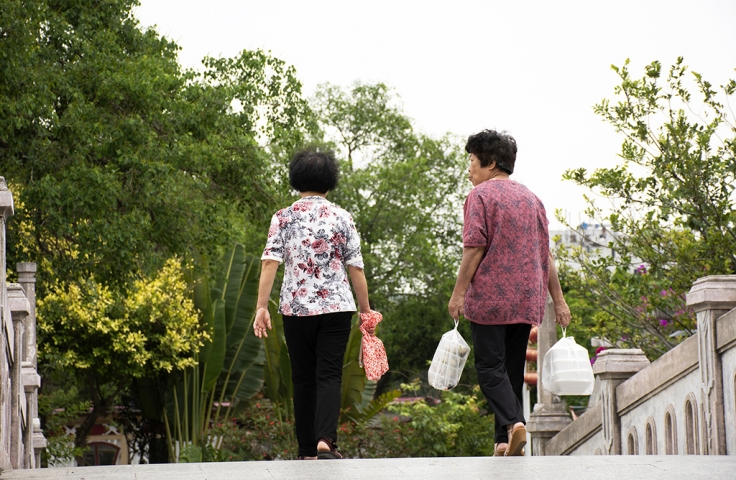 Chinese old women people walking holding food in plastic bag relaxing on bridge in garden at Zhongshan Park in Shantou city