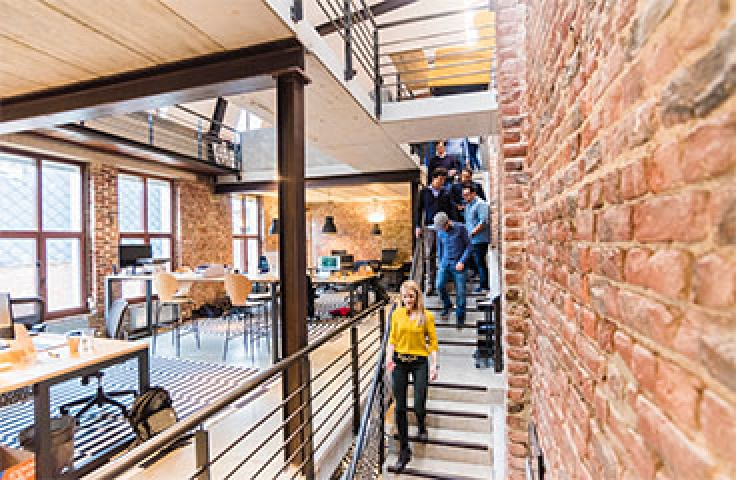 Colleagues walking down stairs in exposed brick office