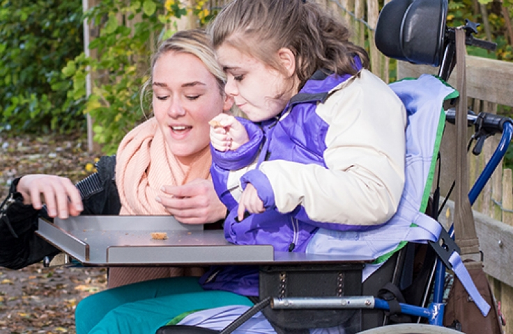Caregiver and child with a disability in a wheelchair