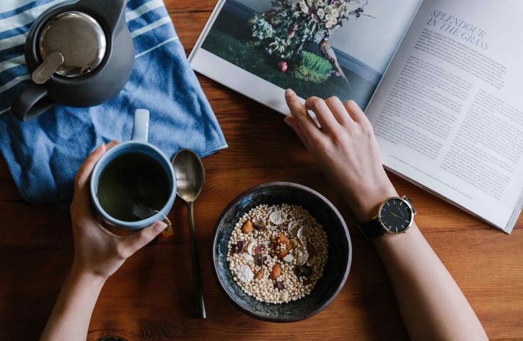 Overhead photo of muesli bowl, tea cup and pot and magazine with a person's arms. Photo: Unsplash