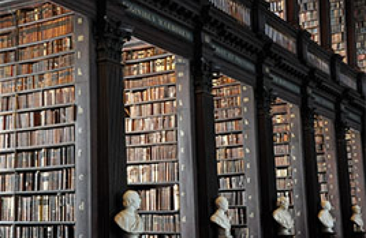 Historic library with busts of famous philosophers and historical texts lining the walls