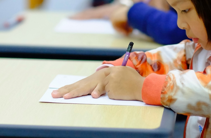 Young girl in orange floral jacket writing on a piece of paper in a classroom