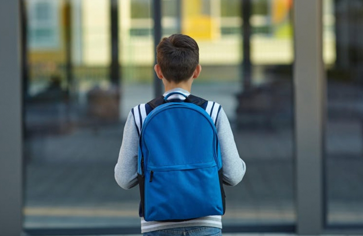 boy with blue bag standing outside doors