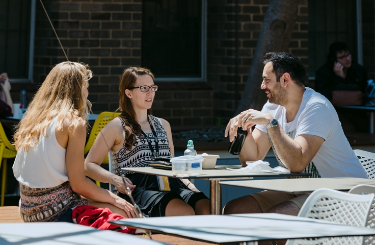 Students sitting outdoors at a table talking