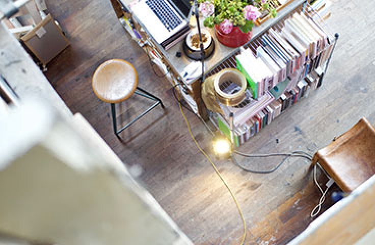 Overhead of vibrant office surrounded by plants, books and lamps