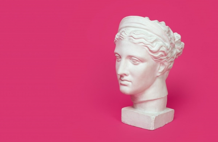 Ancient Greek bust of a woman on a pink background