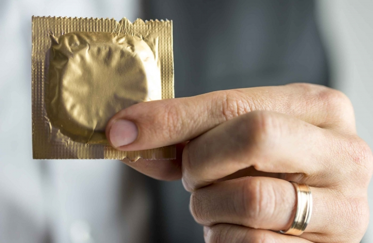 Close-up of a man's hand holding a gold condom packet.