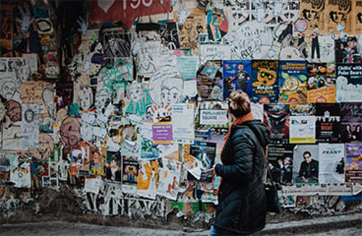 Woman looking at wall of posters on the street