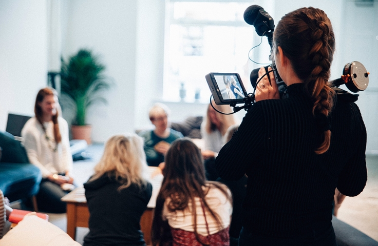Woman filming a group of students for media