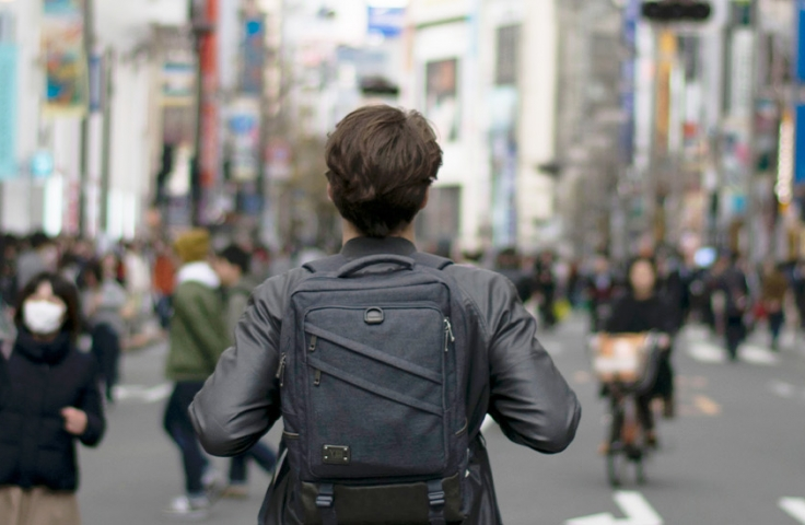 Man with leather jacket and black bag walking down a road