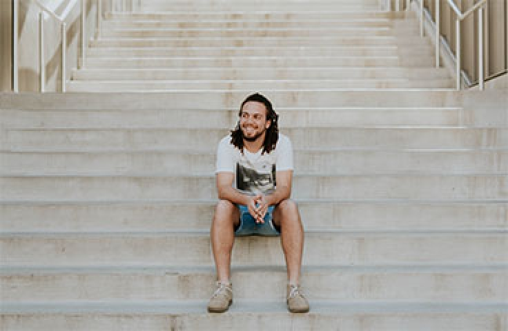 Smiling man with dreadlocks sitting on stairs