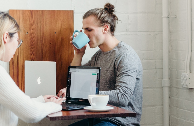 Man drinking coffee from a blue cup and sitting with woman on laptop